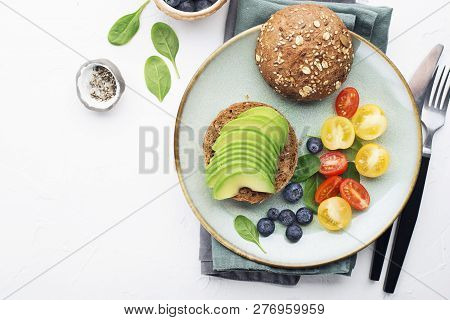 Toasts With Avocado On A White Plate On A Light Background With Colored Tomatoes And Blueberries. He