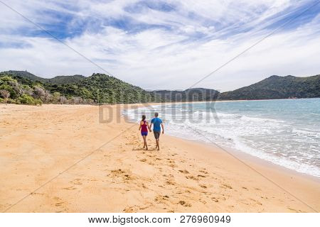 Abel Tasman National Park beach tourists hikers tramping on coast track trail, famous travel destinatinon. Wilderness reserve at the north end of New Zealand's South Island.