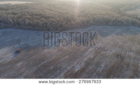 Aerial View Winter Landscape Snow Covered Field And Trees, Town With Buildings In Countryside. Winte