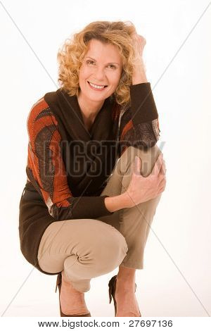 fashionable elderly woman sitting in a squatting position