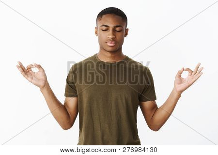 Studio Shot Of Calm And Peaceful Young African American Sportsman Standing In Lotus Pose Searching N