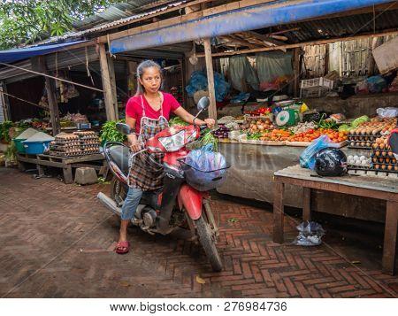 luang prabang, laos - november 20, 2018: woman goes shopping with motorbike at the market in luang prabang.