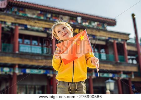 Enjoying Vacation In China. Young Boy With National Chinese Flag On The Background Of The Old Chines