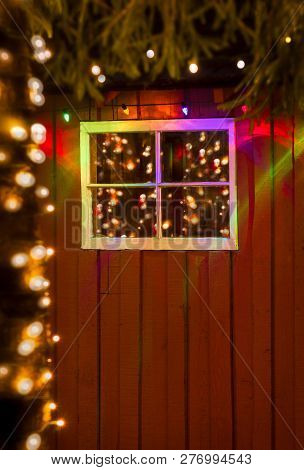 Christmas Lights Reflected In Old Window Of Rustic Red Painted W