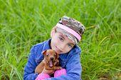little girl with pet puppy mascot mini pinscher in outdoor green grass poster