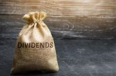 Money bag with the word Dividends. A dividend is a payment made by a corporation to its shareholders as a distribution of profits. Concept business finance and investment. Saving money. Dividend tax poster