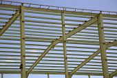 steel frame of a large new factory unit under construction poster