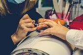 Manicurist applying red nail varnish. Manicure master painting female finger with close up. Manicure and fingers care. poster