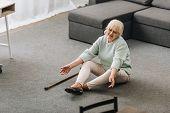 helpless senior woman with blonde hair sitting on floor near sofa poster