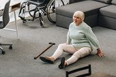helpless senior woman with blonde hair sitting on floor near sofa and wheelchair poster