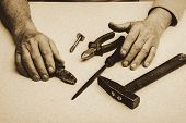 Table composition with tools (nippers, hammer, pliers, rasp, bolt) and hands of elderly working man in sepia tones. Monochrome background. poster