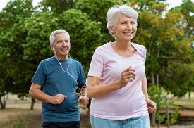 Senior couple running outside at park. Elderly man and old woman jogging together. Retired man and active woman exercising outdoor.