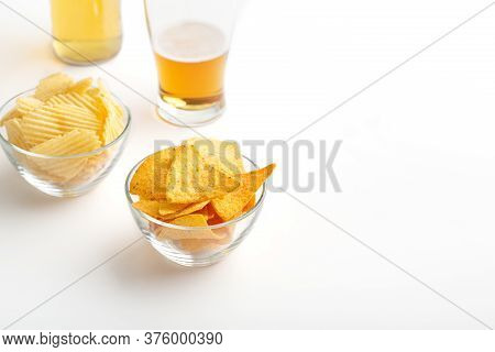 Beer Set. Unfinished Glass Of Beer, Bottle With Light Lager, Chips And Nachos In Glass Plates On Whi