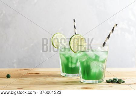 Two Glasses Of Refreshing Lemonade With Chlorella And Lime On A Wooden Table.
