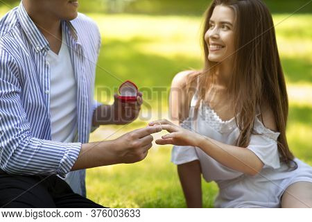 Romantic Proposal. Millennial Man Putting Ring On His Beautiful Girlfriends Finger At Park