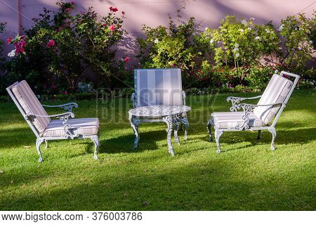 Three Lawn Chairs Surround A Wrought Iron Table In The Garden Of A South African Hotel.
