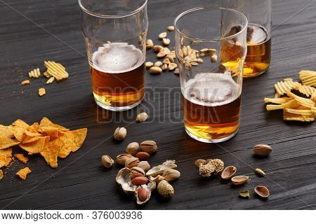 Beer Draft Business. Unfinished Glass Of Beer And Bottle With Drink, Around Are Peanuts, Chips And N