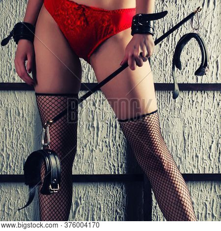 Bdsm Outfit For Adult Sex Games. A Young Woman In Fishnet Stockings With High Heels Is Holding Shack