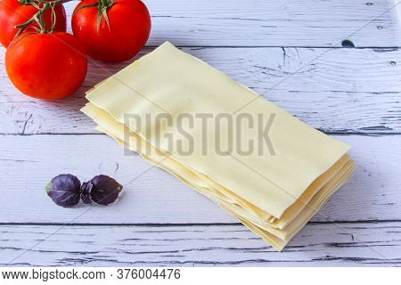 Lasagne Sheets Pasta With Tomato And Basil Leaf On A Wooden Background. Ingredients For An Italian R