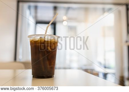 Close Up Of Take Away Plastic Cup Of Iced Black Coffee (americano) In Restaurant On Wooden Table Wit