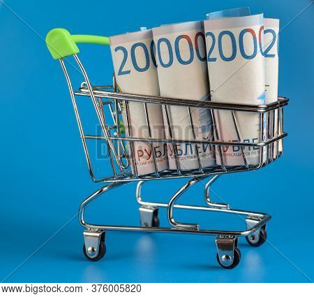 Russian Rubles In A Trolley On A Blue Background. Grocery Basket And Russian Rubles. Russian Currenc