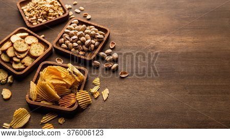 Rusks, Chips, Nuts And Pistachios. Snacks In Square Plates On Wooden Table Background, Panorama, Fre