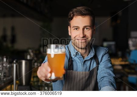 Pint Ale. Smiling Fashionable Barman In Apron Holds Out Glass Of Light Beer In Interior Of Pub, Clos