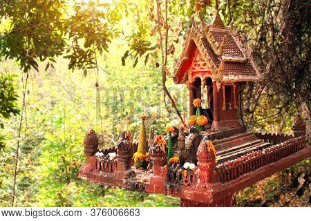 Traditional spirit's house in tropical jungle, Laos. Small altar for spirits in the form of a miniature temple to which bring daily offerings