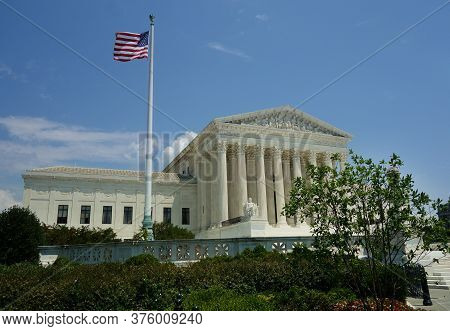 The Us Supreme Court Building In Washington Dc With The American Flag Flying Against Blue Sky