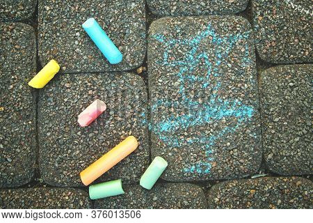 A Childs Drawing And Colorful Chalks On A Street, A Sidewalk Or A Pavement. Childrens Drawing With C