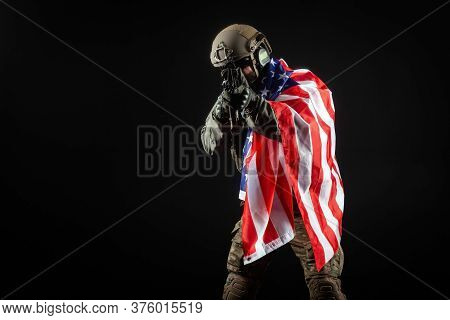 American Soldier In Military Uniform With A Gun Holds The Usa Flag Against A Dark Background, The El