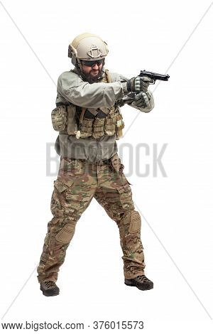 Soldier In Military Equipment With A Gun On A White Background, A Commando In Uniform With A Gun To
