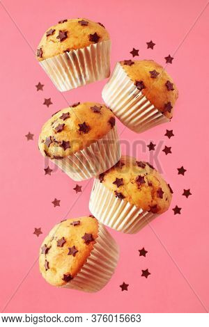 Soft, fluffy, chocolate chip vanilla muffins in paper liners,  on pink background.