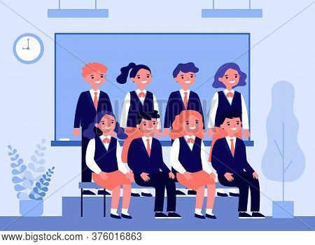 Happy Students Posing For Photo In Classroom. Cheerful Teen Girls And Guys In School Uniforms Sittin