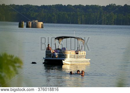 Jamestown Beach, Virginia, U.s.a - June 28, 2020 - Visitors On A Pontoon Boat By The Shallow Water