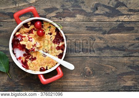 Homemade Crumble With Cherries And Nuts On A Wooden Background. View From Above.