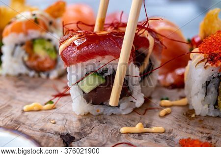 Japanese Food, Eating Sushi Or Sashimi Made From Rice With Salmon, Avocado, Cucumber, Red Fish Cavia