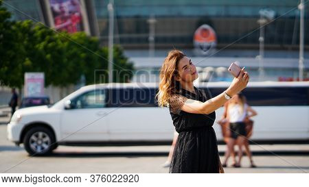 Young Beautiful Woman With Loose Brawn Hair Holding Phone On Background Of White Limousine