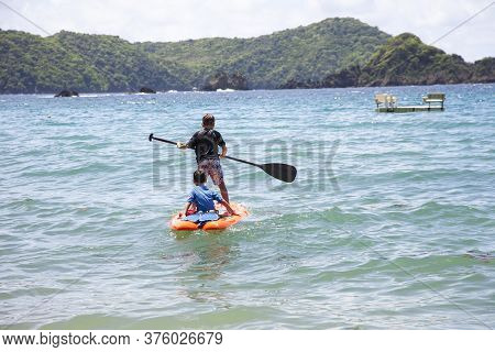 Boys On A Floating Board With An Oar In The Bay. Subtropics Of The World Tourism.