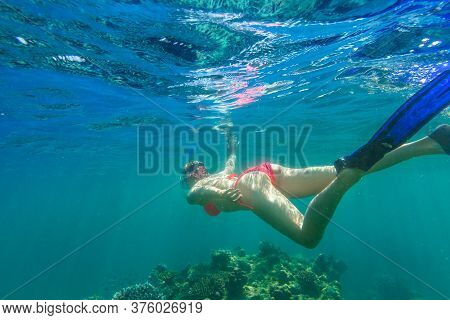 Woman Snorkeling In Red Bikini In Coral Reef Of Surin Islands, Andaman Sea, North Of Phuket, Phang N