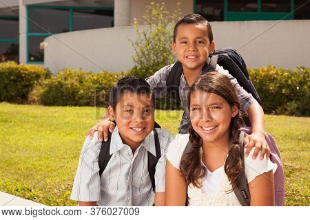 Young Hispanic Student Children Wearing Backpacks On School Campus.