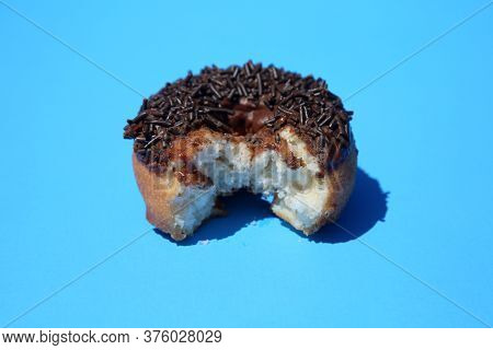 Donut. Cake Donut with Chocolate Frosting and Chocolate Sprinkles. Donut with bite taken out on a blue background.