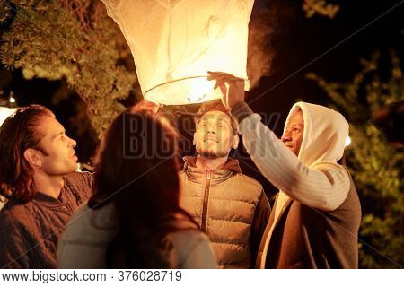 Friendly young intercultural men and woman looking into illuminated large white balloon at night gathering in natural environment