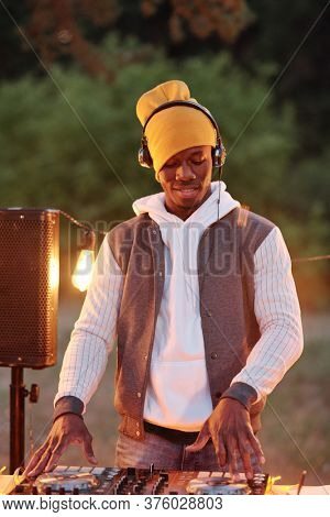 Young African man in stylish casualwear and headphones mixing sounds on turntables while standing by table with stereo board outdoors