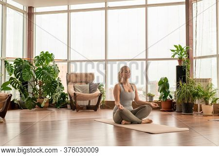 Young serene blond woman in sportswear crossing legs while sitting on mat in pose of lotus and practicing meditation exercises at home