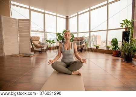 Young active blond sportswoman crossing legs while sitting on mat in pose of lotus and practicing meditation exercise in domestic room