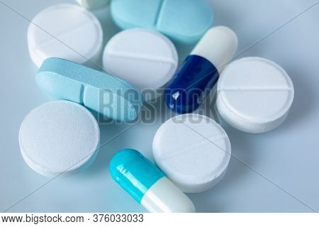White And Blue Tablets And Pills On A Light Background. Medical Concept. Selective Focus