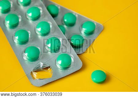 Blisters Of Green Pills And Separately One Pill On A Yellow Background. Concept Of Starting A Course