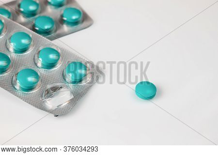 Blisters Of Green Pills And Separately One Pill On A White Background. The Concept Of Starting A Cou
