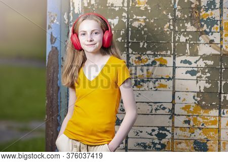 Youth And Teens Lifestyle. Positive Teenage Girl In Red Wireless Headphones Posing In Casual Outfit